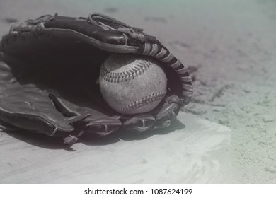 Black and white vintage baseball in players glove laying on homeplate, ball field dirt in background.