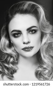 Black and white vintage style portrait of young beautiful woman with blonde curly hair