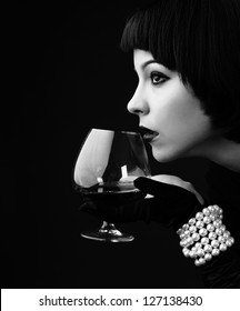 black and white: vintage styled portrait of a young beautiful woman with glass of alcohol