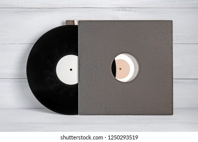 A black and white vinyl record for a turntable with a gray covers white wooden background of their boards. Listening to Christmas songs
