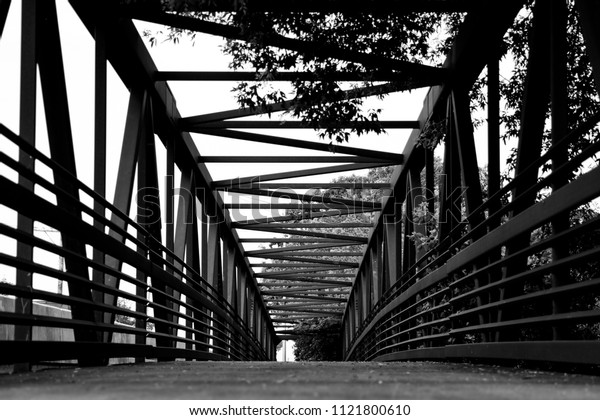 Black and white walking bridge going over a river.