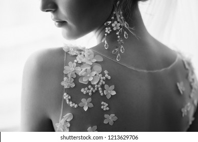 Black and white wedding photo of bride in wedding dress with luxury earrings jewelry