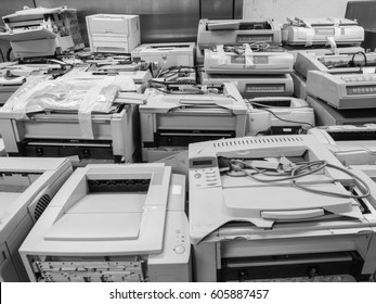 Black and white wide shot of pile or stack of old printers that are out of date. Outdated old printers are waiting for an auction or sell away as office trash