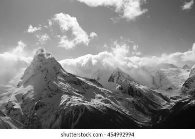 Black and white winter mountains with clouds. Caucasus Mountains, region Dombay.
