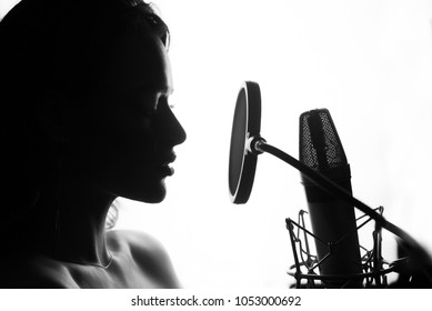 Black and White. Woman singing in the recording studio. Profile of a woman with a beautiful face and lips.