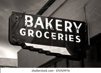 Black and White Worn Bakery and Groceries Sign in Small Town