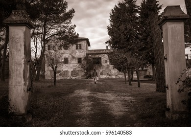 black & white young man with a suitcase walking in front of a creepy  old abandoned house