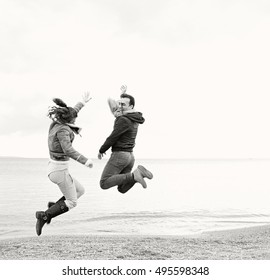 Black and white youthful happy couple jumping playfully on beach on a autumn winter holiday, wearing jackets and having fun together, nature outdoors. Active recreation travel lifestyle.
