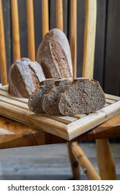 Black whole wheat sourdough bread on a wooden chair