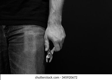 Black and whtie detail of a man wearing jeans and a t shirt holding a pair of pliers at his side