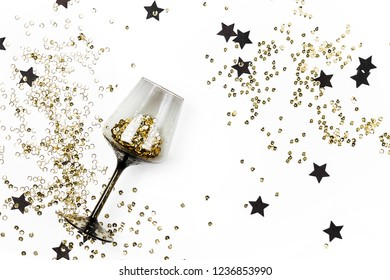 Black wine glasses with golden confetti and black stars on white background. Flat lay, top view. Holyday and celebration concept.