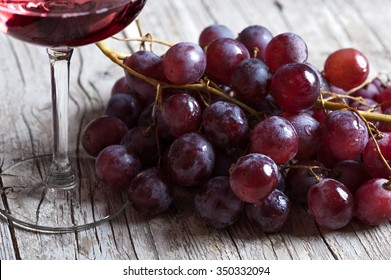 Black wine grapes on rustic wooden table
