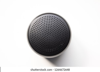 Black Wireless Bluetooth Speaker Isolated on Plain White Background, Viewed From Above; Top View Showing Perforated Metal Grille Holes