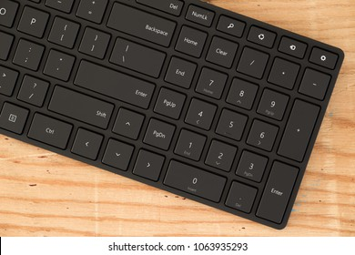 black  wireless computer keyboard on wooden table