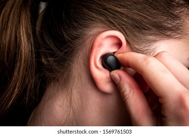 Black wireless headphones in ear.