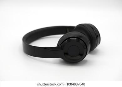Black wireless headphones on awhite isolated background.
