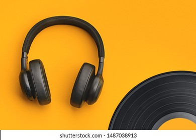 Black wireless headphones with vinyl record on a colored background. Music concept with copyspace. Headphones on orange background isolated