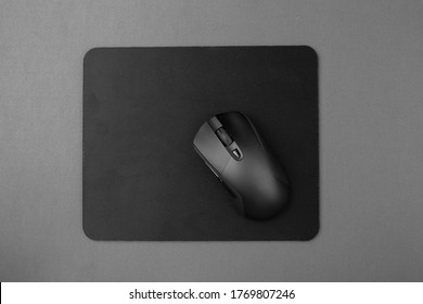 Black wireless mouse on a mouse pad, top view.