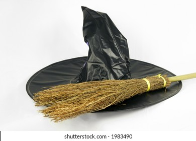 A black witch hat and broomstick isolated on a white background
