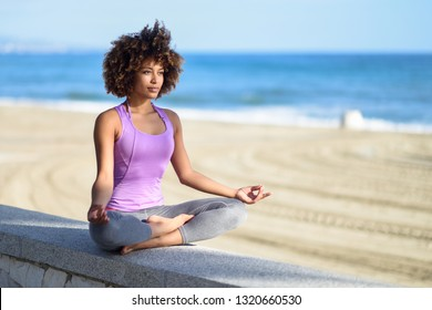 Black woman, afro hairstyle, doing yoga in the beach. Young Female wearing sport clothes in lotus figure with defocused background.