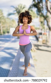 Black woman, afro hairstyle, doing yoga in the beach. Young Female wearing sport clothes.