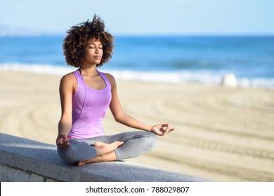 Mulher negra, penteado afro, fazendo yoga asana na praia com os olhos fechados. Jovem Feminino vestindo roupas esportivas em pose de lótus com fundo desfocado.