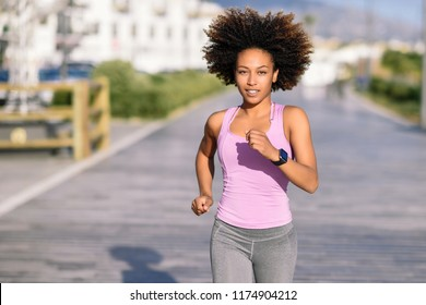 Black woman, afro hairstyle, running outdoors in urban road. Young female exercising in sport clothes.