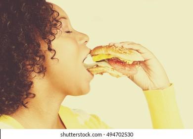 Black woman biting hamburger sandwich