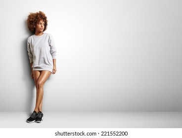 black woman with curly hair wearing sweatshirt like a dress
