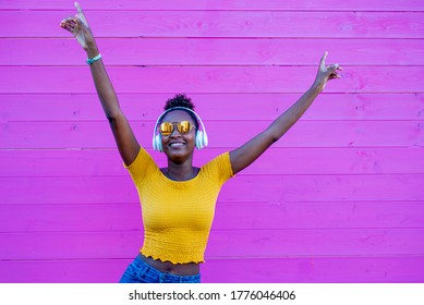black woman dancing smiling, pink background in contrast with yellow clothes and jeans, afro fashion girl with headphones to listen to music