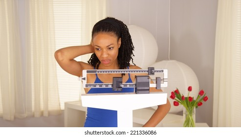 Black woman disappointed after checking weight