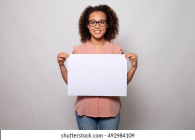 Black woman displaying white banner isolated on background