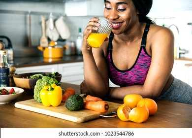 Black woman is drinking orange juice