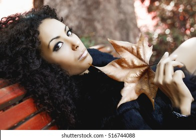 Black woman with a dry leaf in an urban park. Beautiful female with afro hairstyle. Young girl wearing autumn clothes.