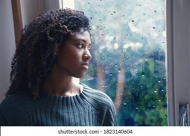 Schwarze Frau, die sich unter Depressionssymptomen allein zu Hause fühlt