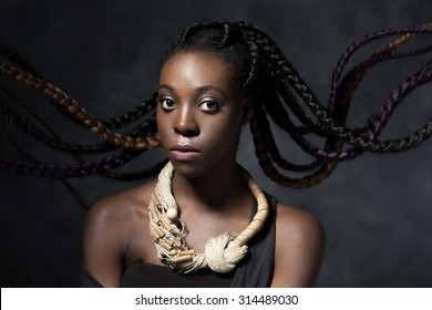 the Black woman with the flying long hair braided in multi-colored braids. Studio photo. Stylish ethnic accessory of handwork and unusual hairstyle.