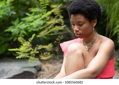 Black woman in a garden thinking
