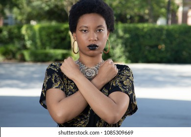 Black woman with her arms in an X
