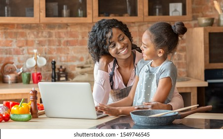 Black woman and her cute daughter embracing and reading recipe on laptop, cooking at kitchen, copy space