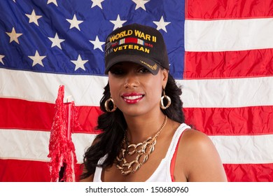 black woman in her grandfathers hat, remembering and taking pride in his service to the United States in WW 2
