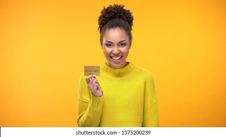 Black woman holding golden credit card, VIP banking programs for rich people