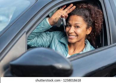 Black woman holding keys to new car and smiling at camera