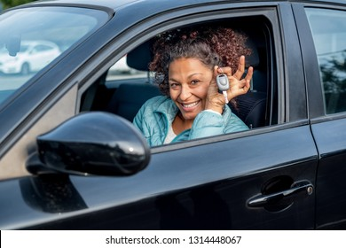 Black woman holding keys to new car and smiling at camera