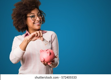 black woman holding a piggy bank and bills