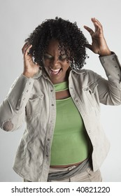 Black woman laughing hysterically with hands thrown in the air