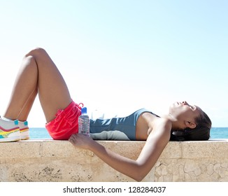 Black woman laying down on a stone wall by the sea, having a break from exercising and sport against a deep blue sky background.