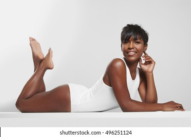 black woman lies on a cosmetology massage table in a white room