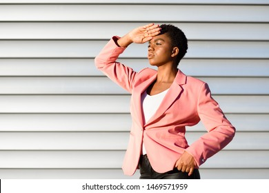 Black woman, model of fashion, standing on urban wall. African american female wearing suit with pink jacket with sunset light.