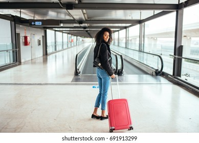 black woman in the moving walkway at the airport with a pink suitcase.