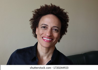 Black woman with natural hair smiling and wearing a black shirt.